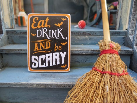 """Front porch steps with broom stick, red cake pop, and sign reading """"Eat, Drink, and be Scary"""" leading up to a Halloween party"""