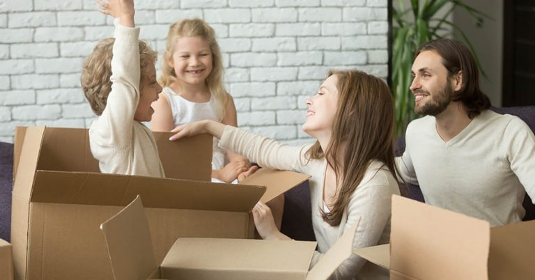 A family plays with moving boxes.