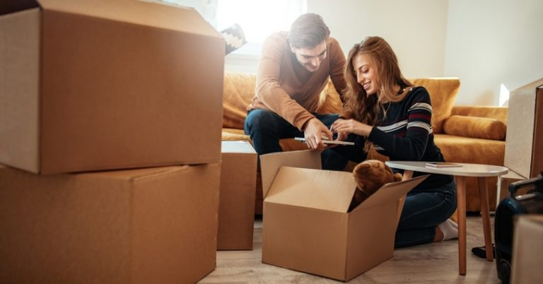 a couple is bent over moving boxes and checking something off a list