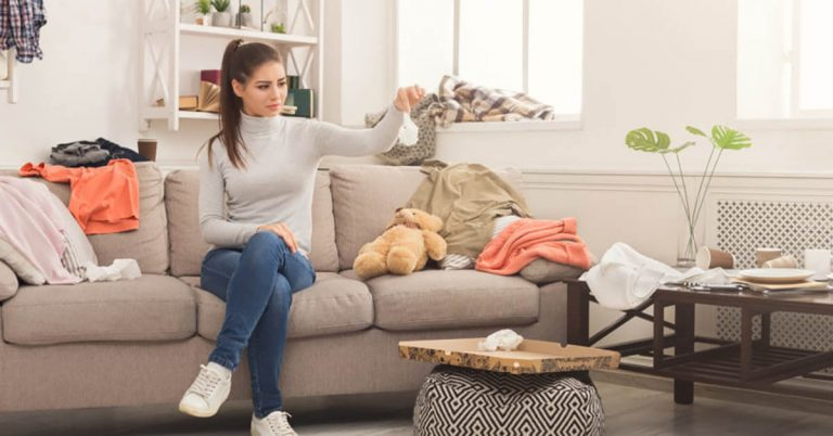 A woman cleans up her messy living room.