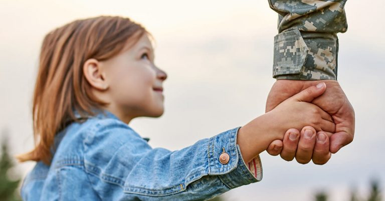 A father in the military holding hands with his daughter.