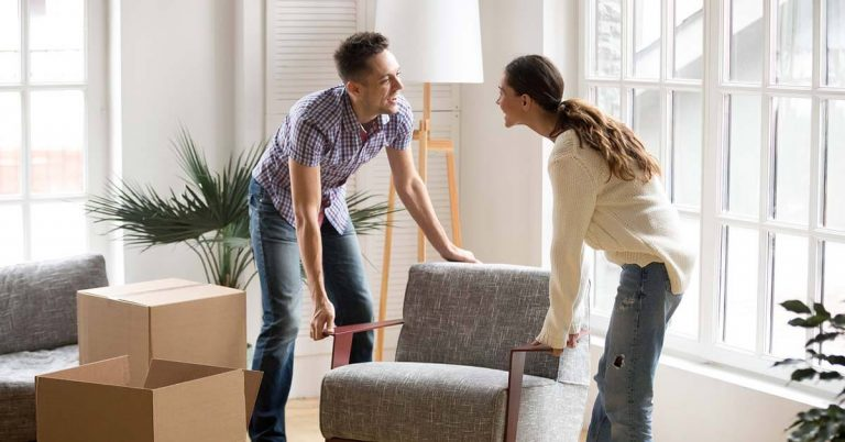 A couple move a chair into their new home.