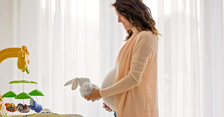 A pregnant woman lovingly places a plush bunny in a crib.
