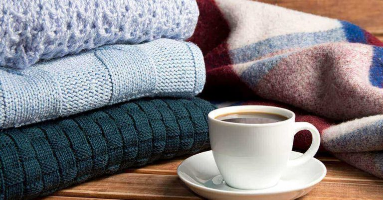 A stack of sweaters sits on a wood table next to a cup of coffee.