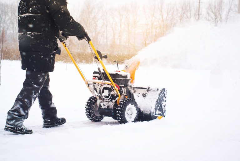 A man pushing a snowblower against a landscape of white.