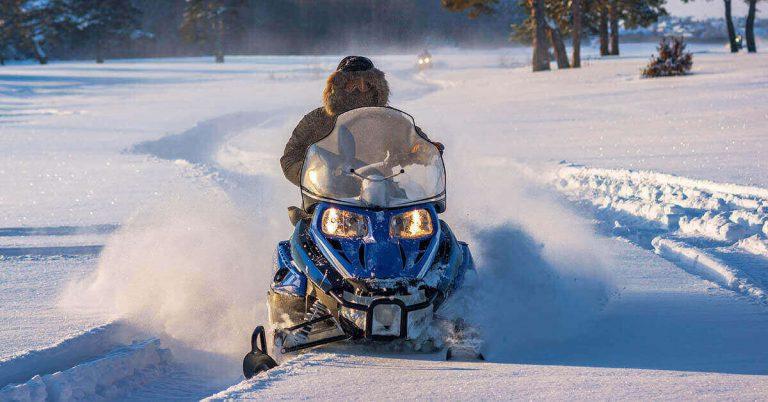 A person on a snowmobile races through a snowy field.