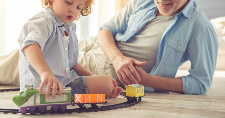 A grandfather plays toy trains with his grandson.