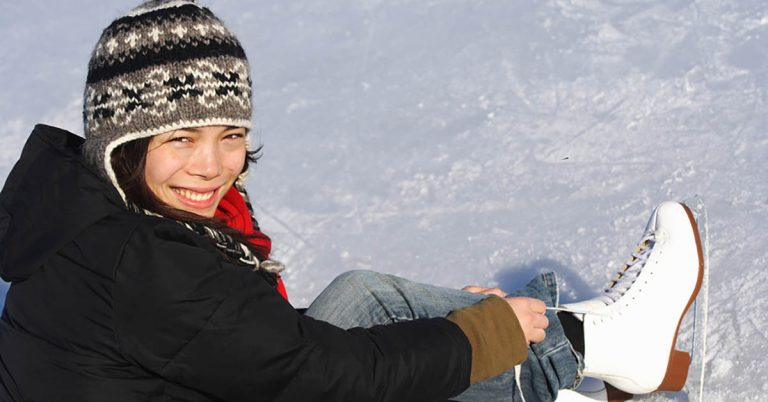 A woman smiles as she ties her ice skates.