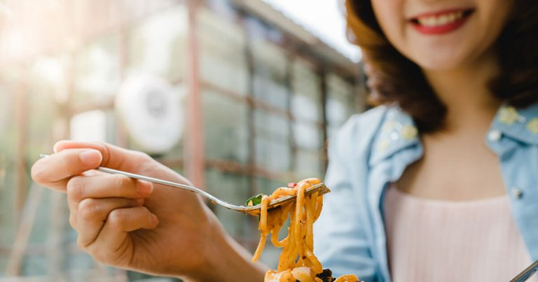 A close-up shot of a woman eating a plate of pasta