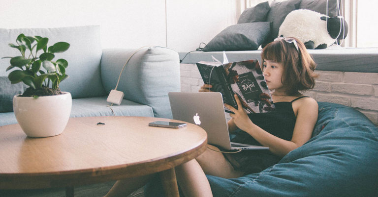 a young woman reads in a bean bag chair