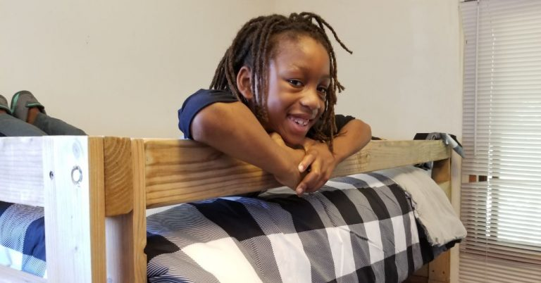 young child smiling in a bunk bed provided by sleep in heavenly peace