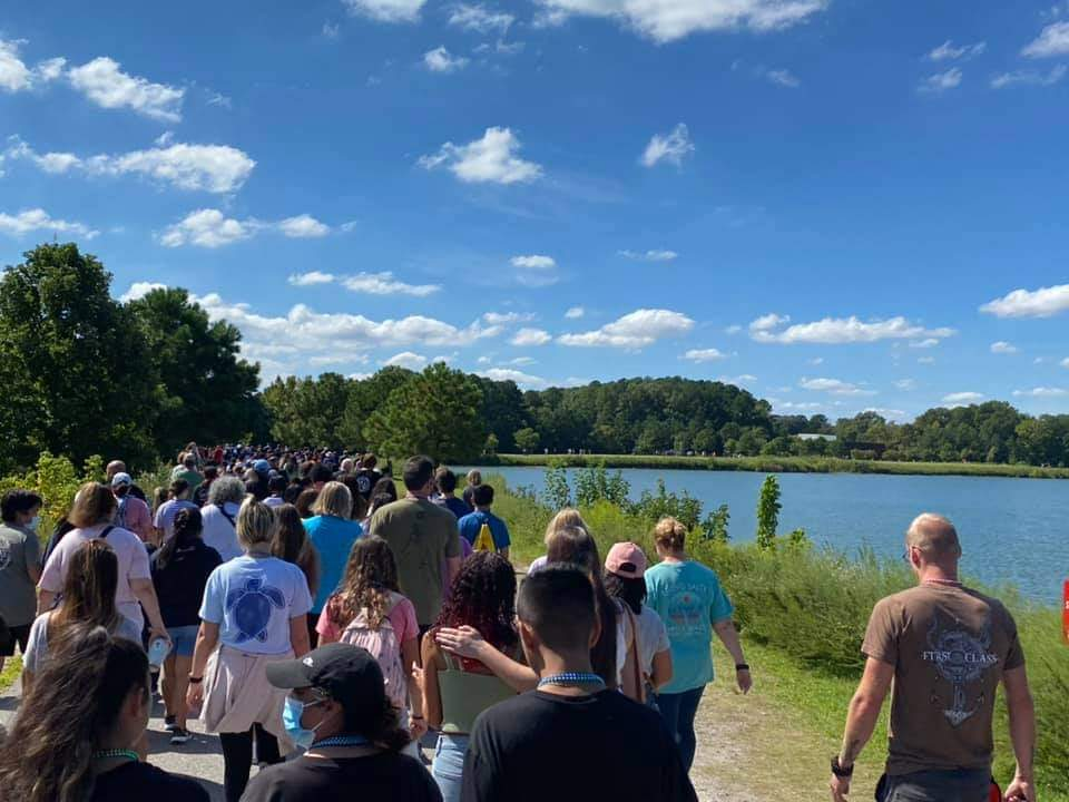 A large crowd of people walking by a lake to raise funds for suicide awareness.
